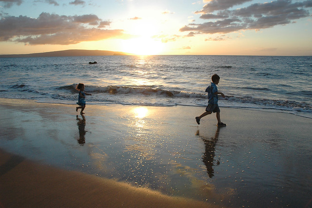 One kid chases after another on a beautiful beach with a Hawaiian sunset