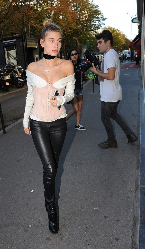 cream off the shoulder Mugler sweater with a pink Balmain corset over it, black leather pants with matching Alaia boots, black velvet chocker and multiple necklaces