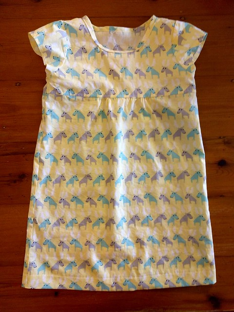 A child's dress. Fabric is yellow with moose print.