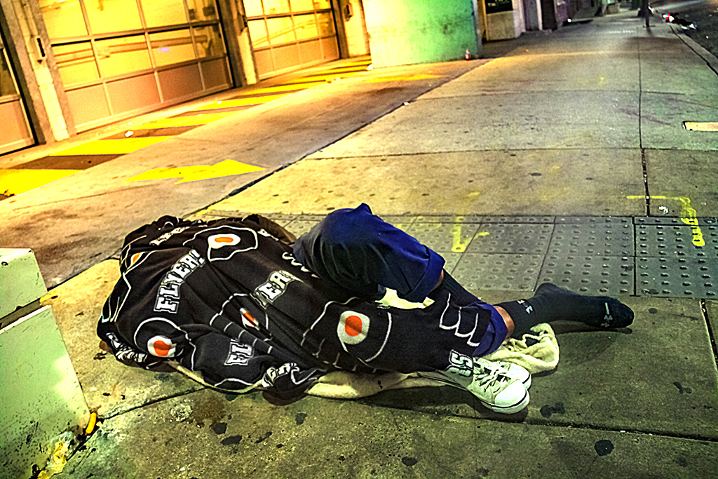 Man sleeping outside parking garaga under Flyers blanket--Center City