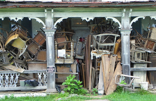 Front porch of a house piled full of junk | by FastFords