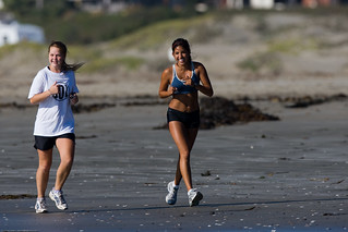 Two young girls jog along Morro Strand State Beach - Ethnic Diversity depicted | by mikebaird