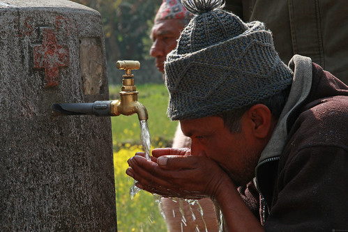 A villager of Kaski shows how well the water tap work | by World Bank Photo Collection