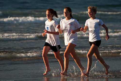 Three high school girls, as part of a larger group, run up and down the beach | by mikebaird