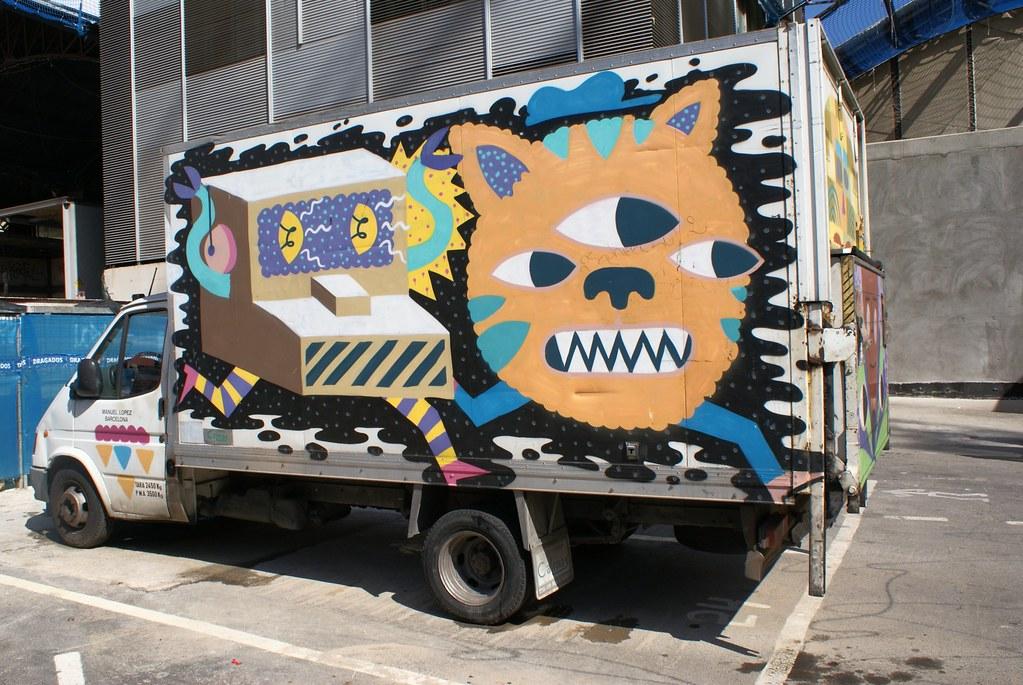 Street art à la Boqueria : Une caisse enregistreuse poursuivi un chat à 3 yeux.