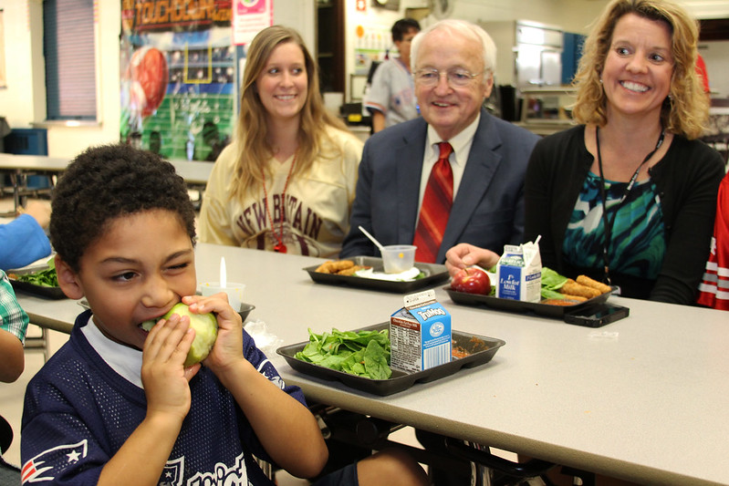 Under Secretary Kevin Concannon, center, watches on as a student takes a bite of his apple