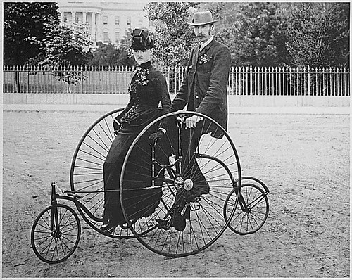 Smartly dressed couple seated on an 1886-model bicycle for two. | by The U.S. National Archives
