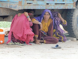 Sheltering under trucks | by United Nations Development Programme