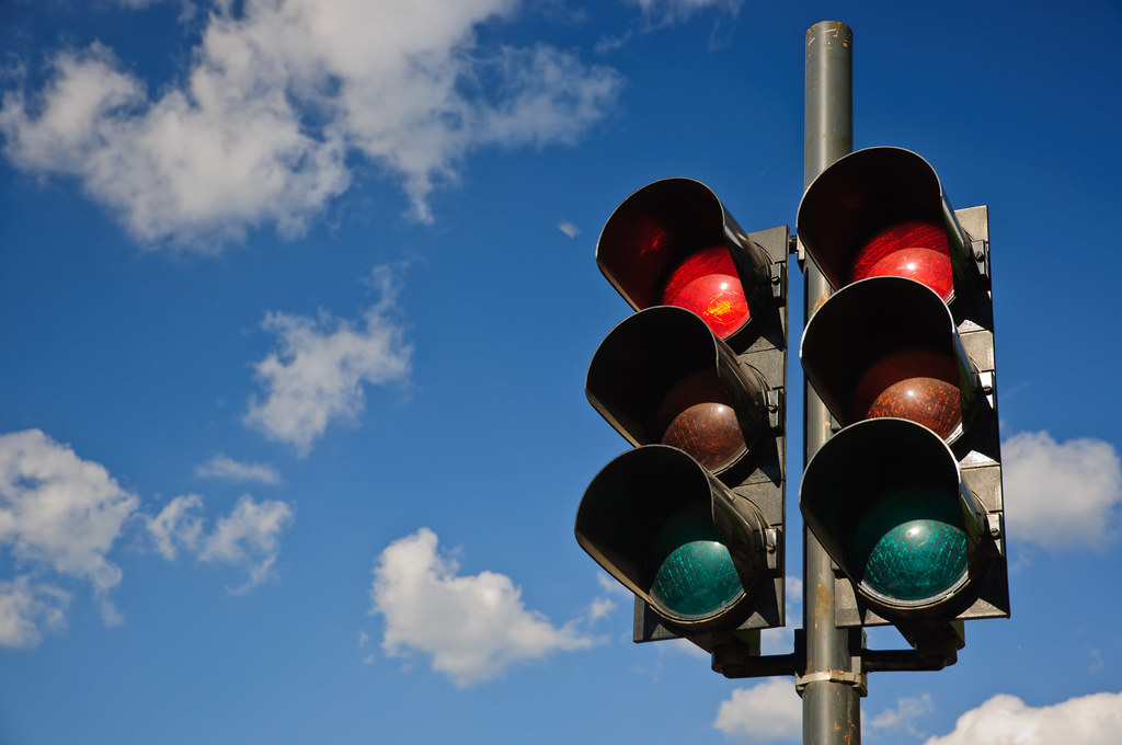 A couple of red traffic lights against a blue sky
