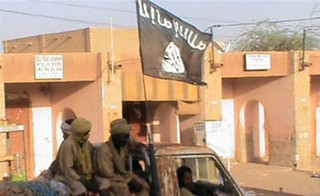 Photograph of a truck carrying members of the Islamist Ansar Dine of northern Mali. There is a black flag symbolizing their Islamic orientation flying overhead on the vehicle. | by Pan-African News Wire File Photos