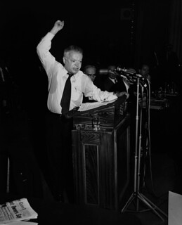 David Dubinsky gestures emphatically while making a speech, with Julius Hochman and others on the stage, March 1958. | by Kheel Center, Cornell University