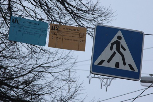 Tram and trolleybus stop signs hang from overhead wires