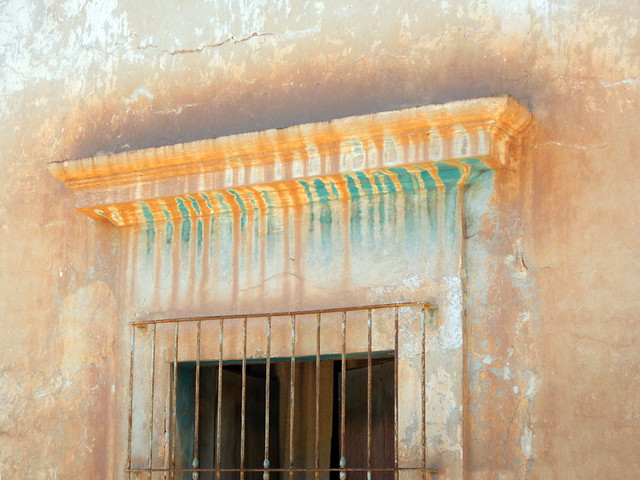 A coloured wall and barred window in Mascota, a 'Pueblo Magico' on the Sierra Madres Occidental on the Pacific coast of Mexico