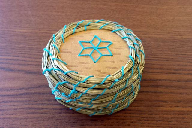 small round basket with blue thread