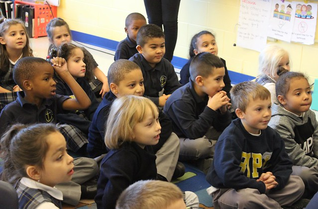 Elementary school scholars listening attentively in class