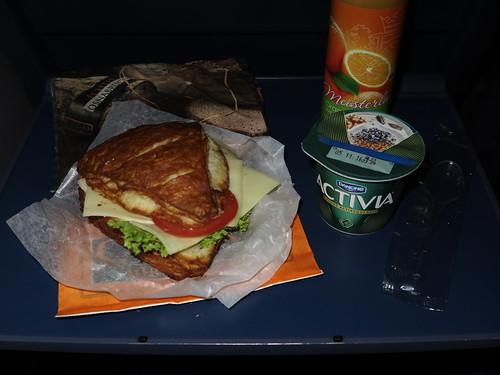 Vegetarisch belegte Laugenecke von der Bäckerei Coors (Osnabrück Hbf) mit Orangensaft (Meisterland) und Joghurt (Danone) als Frühstück im Zug