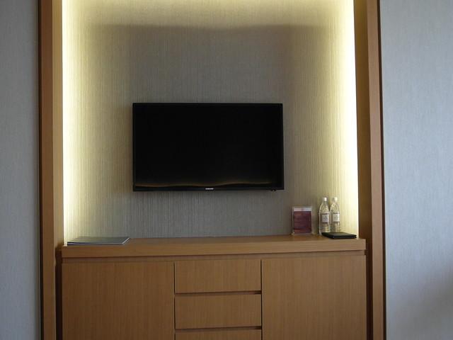 大電視的左下方是 room service 菜單,右下方是贈送的瓶裝水@台中日月千禧酒店