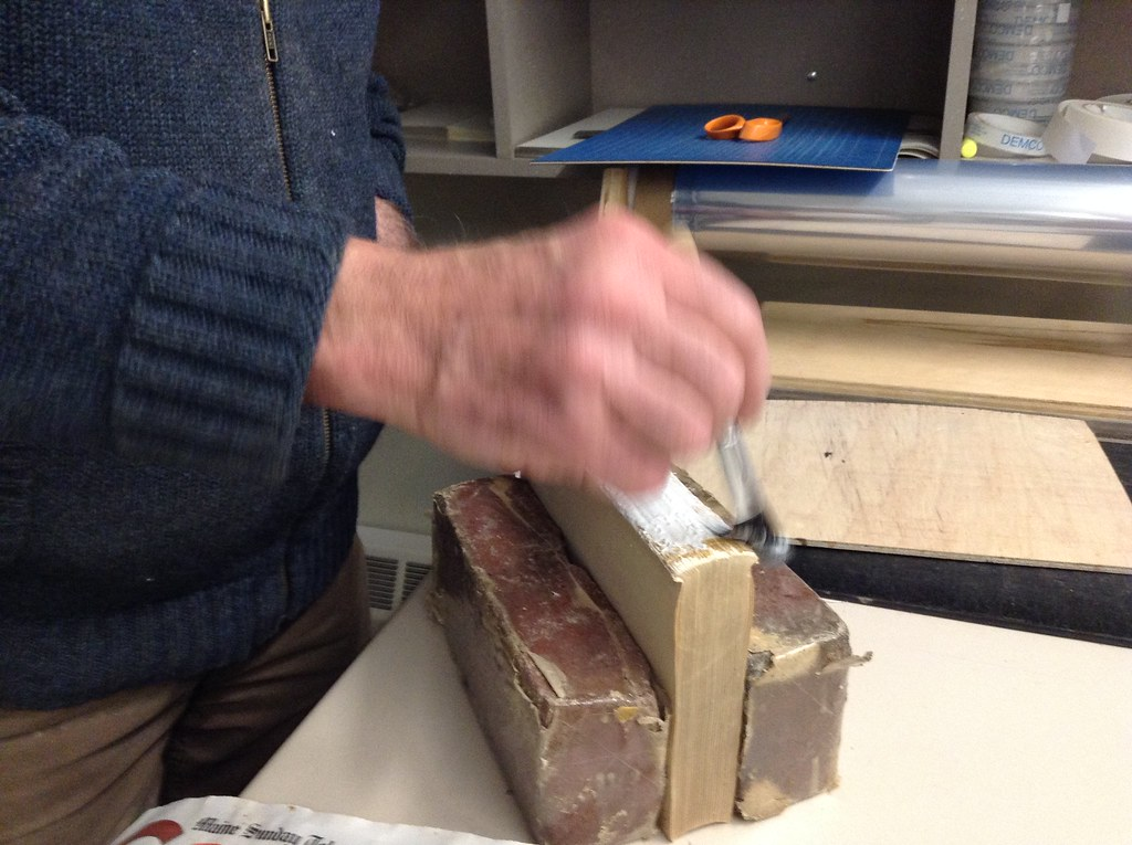 Applying glue to the spine of a book.