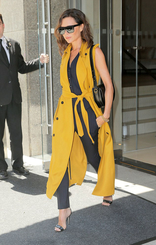 mustard-yellow-long-sleeveless-trench-coat,-pinstripe-waistcoat-with-matching-trousers,-a-pair-of-barely-there-heels-&-oversized-sunglasses
