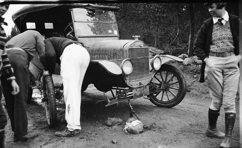Woman watches as men change a tire on a Model T