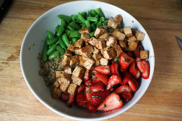 A large white bowl, with a layer of quinoa on the bottom. On top, separate neatly arranged stripes of strawberries, tofu, and snap peas. A composed salad for the moment but we're going to MIX IT UP