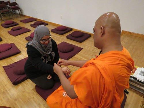 Bhante Devananda offering a blessing thread