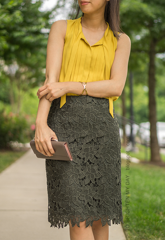 sleeveless mustard yellow pleated top, gold cross bracelet, taupe clutch, olive green lace pencil skirt