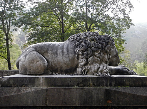 A stone lion statue guarding the entrance way to the Covadonga church and shrine in northern Spain