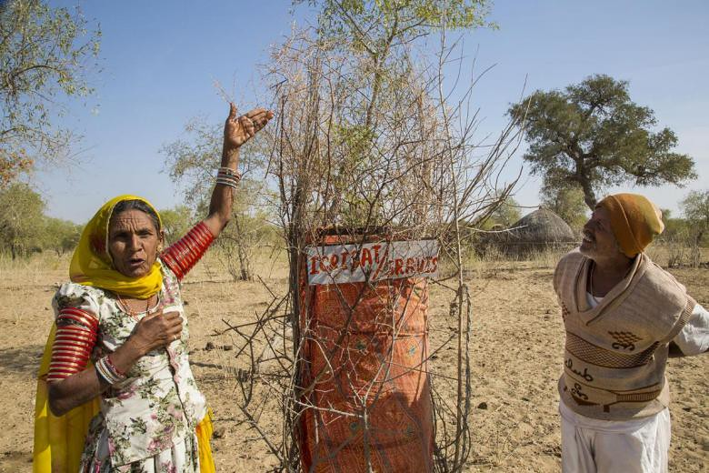 Indian woman demonstrates rainwater-harvesting structure set up in her local village