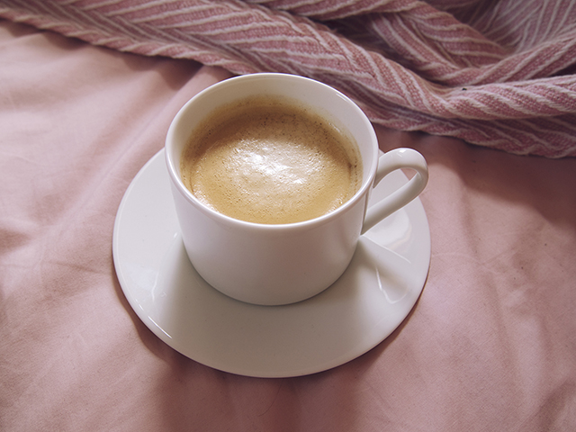 Fresh Nespresso coffee cup and saucer in pink bed blanket