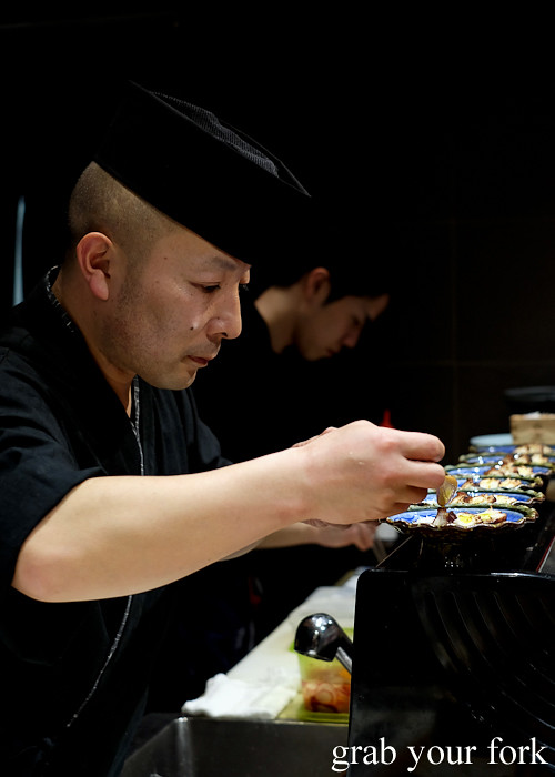 Sushi chef Tomoyuki Matsuya garnishing grilled octopus at Hana Ju-Rin in Crows Nest Sydney