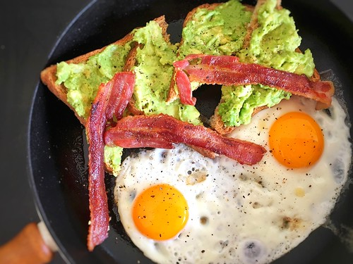 late breakfast of fried eggs and bacon, with smashed avocado on wholewheat toast