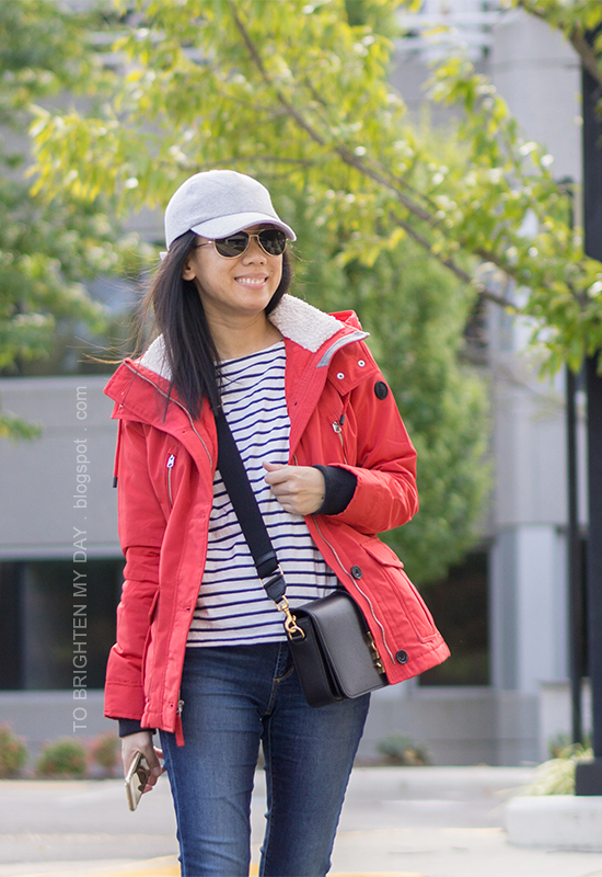 gray baseball cap, red performance jacket, striped top, black crossbody bag, skinny jeans