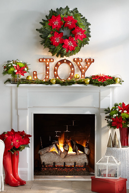 Merry mantel with lighted Joy sign pine cuttings with ornaments a centerpiece boots vase with poinsettias red glass vase with mums and pine wreath over a fireplace and a Christmas terrarium on a red box