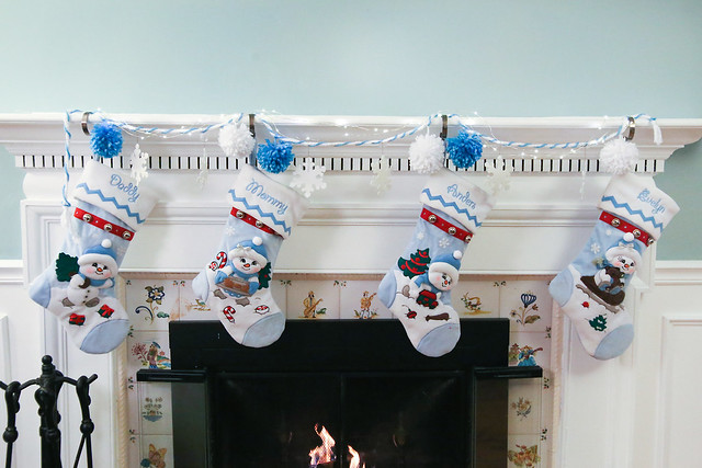 Christmas Mantel with snowball decorations and snowman snowbuddy family stockings in front of fireplace