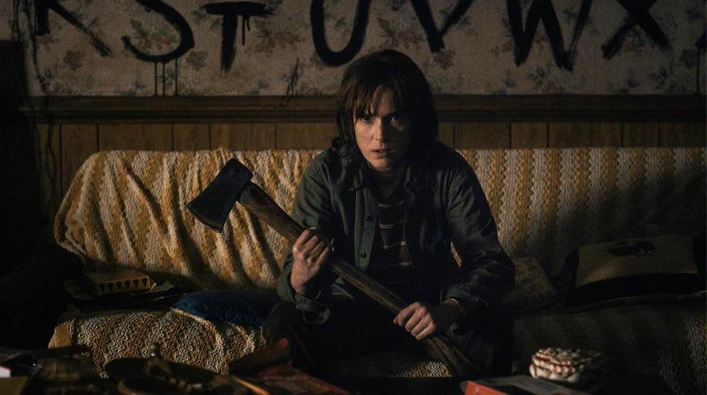 Joyce interpretada por Winona Ryder em Strager Things segura um martelo