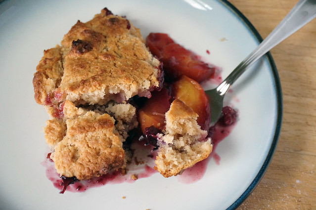 A serving of peach-blueberry cobbler with spiced biscuit crust, the crust broken apart, taunting you with its tender open crumb resting on soft, rich fruit.